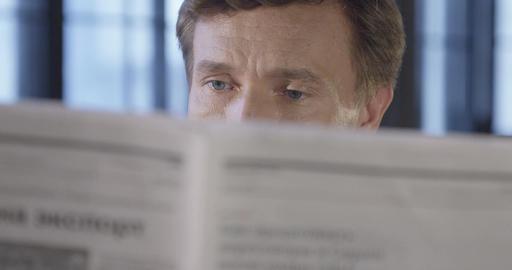 Slow Motion Portrait of Successful Confident Businessman Reading a Newspaper. Cl Live Action