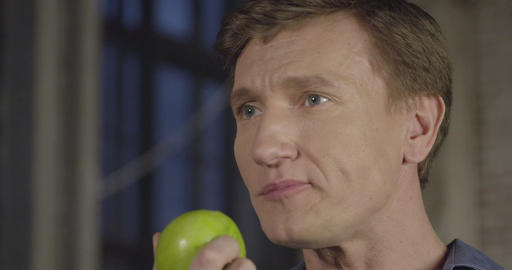 Slow Motion Portrait of a Man Eating Apple. 4K UHD 4096x2160 Footage