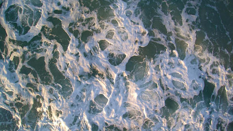 Close view of the sea from above - clear water progressively troubled with sand Footage