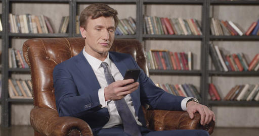 Slow Motion Portrait of Successful Confident Man Calling on Mobile Phone Sitting Footage