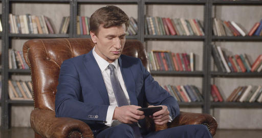 Slow Motion Portrait of Successful Confident Man Typing on Mobile Phone Sitting  Footage