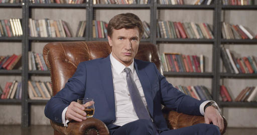 Slow Motion Portrait of Successful Confident Businessman Drinking Whiskey Sittin Footage