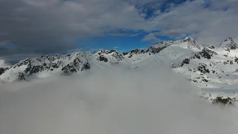 Flying in clouds between snow-capped mountains Footage