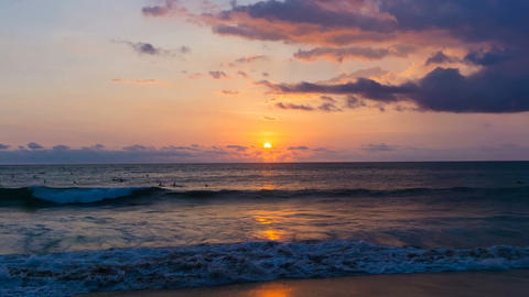 Beautiful gold sunset with purple clouds over surfers in ocean time lapse 4k Filmmaterial