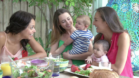 Group Of Mothers With Babies Enjoying Outdoor Meal At Home Footage
