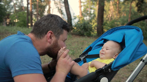 Loving father kissing feet of his baby son in park ビデオ