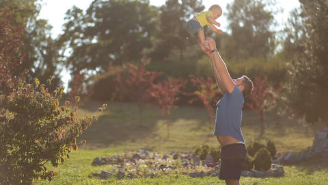 Playful dad throwing baby boy high in summer park Footage