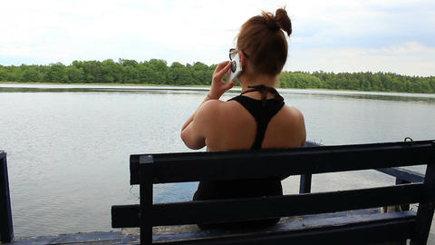 Lonely girl sitting on a bench by the lake talking on mobile phone Footage