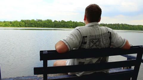 Lonely boy on a bench by the lake looking away ビデオ