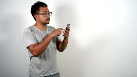 Casual man using smartphone Browsing and Text Messaging Footage
