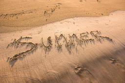 Summer word written in sand フォト
