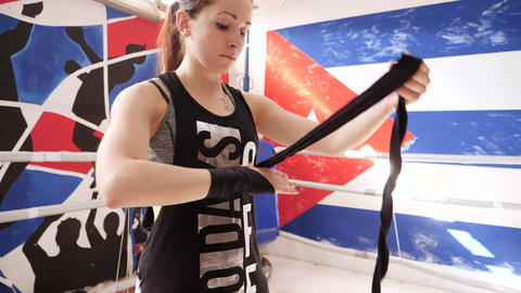 Young girl standing inside the ring wraps her hands in black elastic bandages Footage