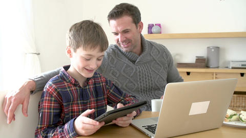 Father Using Laptop And Son Using Digital Tablet At Home Footage