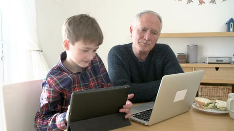 Grandfather Using Laptop And Grandson Using Digital Tablet Footage