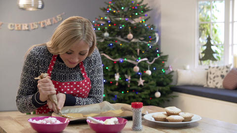 Woman Decorating Christmas Cookies In Kitchen Footage