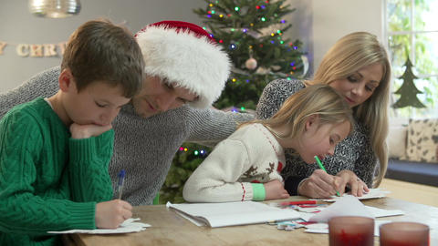 Family Writing Christmas Cards Together At Home Footage