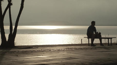 Still shot of a male sitting on a bench next to the river Footage