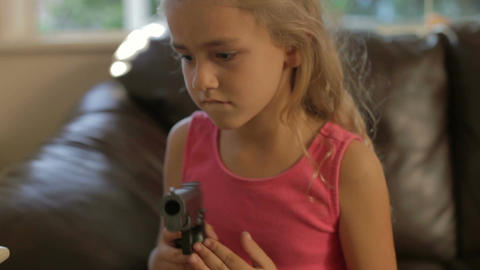 Girl Playing With Parent's Gun She Has Found At Home Stock Video Footage