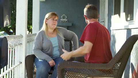 Couple Sitting Outdoors On Porch Arguing Live Action