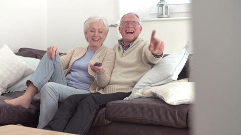 Senior Couple Sitting On Sofa Watching TV Live Action