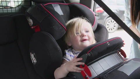 Mother Putting Daughter In Safety Seat On Car Journey Footage