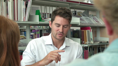 Two Students Working Together In Library With Teacher Footage