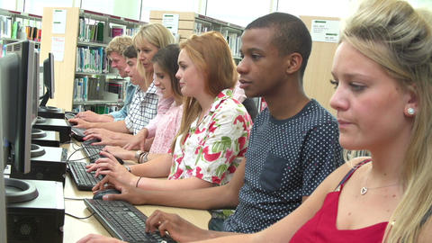 Students Working At Computers In Library With Teacher Footage