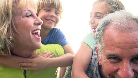 Grandparents Giving Grandchildren Piggyback Ride In Garden Footage