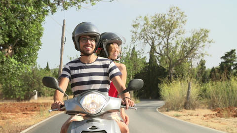 Slow Motion Shot Of Couple Riding Motor Scooter On Road Footage