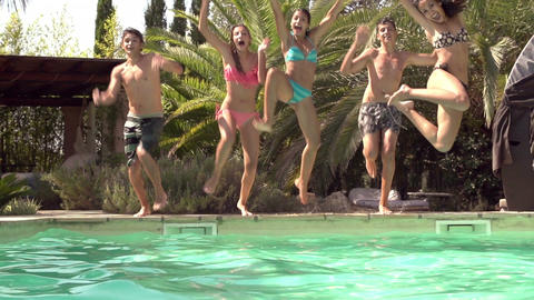 Slow Motion Shot Of Teenagers Jumping Into Swimming Pool Footage