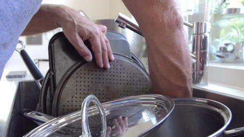 Slow Motion Sequence Of Man Washing Pans In Sink Footage