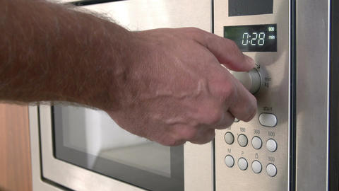Close Up Of Hand Setting Timer On Microwave Oven Footage