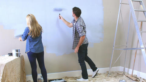 Couple Decorating Room Using Paint Rollers On Wall Footage