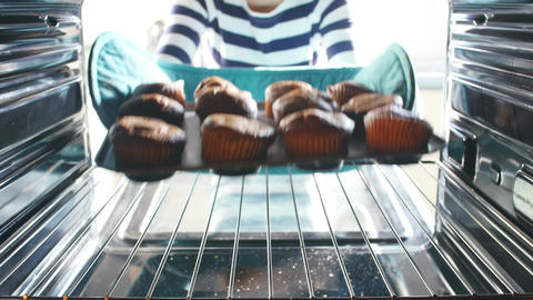Woman Taking Tray Of Baked Muffins Out Of The Oven Footage