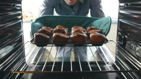 Man Taking Tray Of Baked Muffins Out Of The Oven Footage
