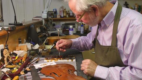 Man Restoring Violin In Workshop Footage