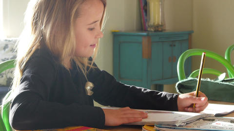 Girl Sitting At Table Indoors Doing Homework Footage