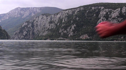 Mountain landscape with rocks covered by dense forests. A man enters the river,  Footage
