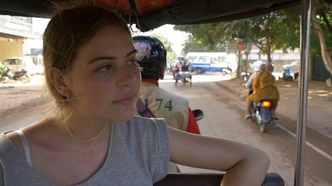 Backpacker tourist girl traveling in asia riding on tuk tuk rural asain villag Footage