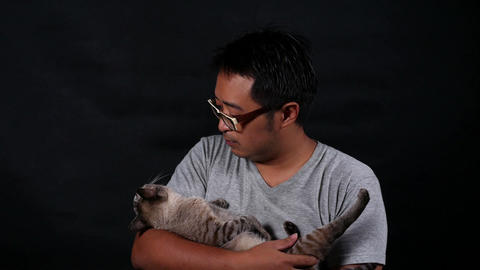 man carry and playing a cat with care. on black background Live Action