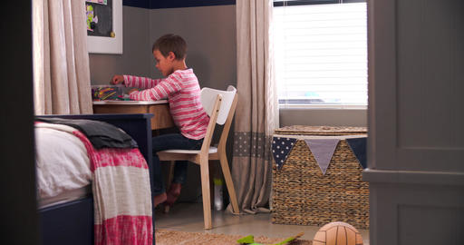 Boy Sitting At Desk In Bedroom Doing Homework Footage