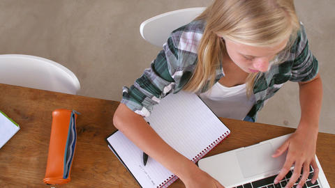 Overhead View Of Girl Doing Homework At Table On Laptop Footage
