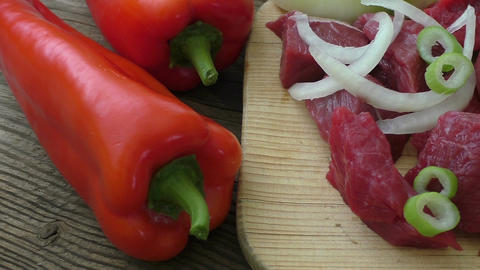 Fresh raw chopped beef on a wooden cutting board with fresh organic vegetables Live Action
