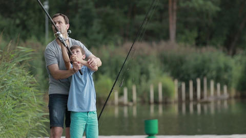 Teenage boy learning to fish with father's help Footage