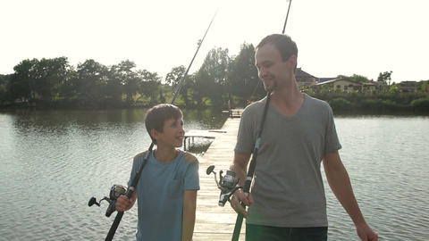 Happy dad and son with rods going fishing on pond Footage