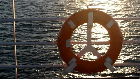 Red lifebuoy on a boat crossing the sea at sunset Filmmaterial
