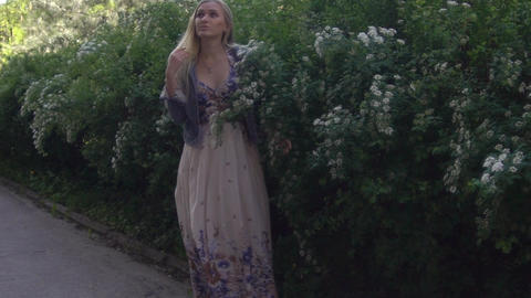 Young Girl Walking Near Brush With White Flowers Tree Slow Motion Footage