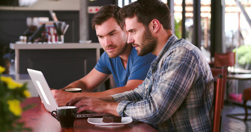 Two Men In Cafe Working On Laptop Together Footage