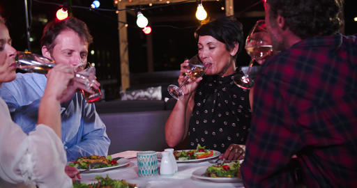 Group Of Mature Friends Enjoying Meal At Rooftop Restaurant Live Action