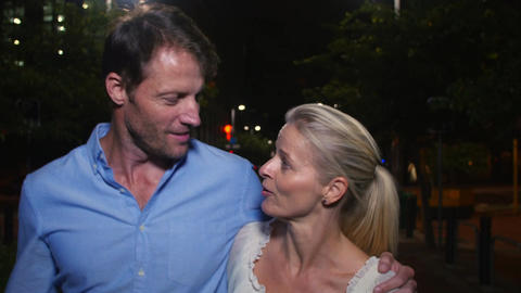 Mature Couple Walking Along Street On Night Out Footage